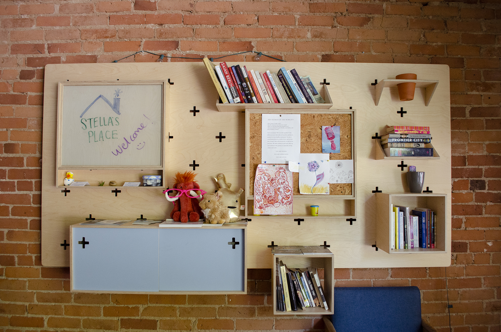A photo of a wall in the Stella's Place café. A very bright and vibrant wooden shelf hung up on the wall has books, stuffed animals, drawings and more plastered all over.