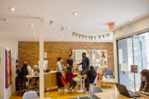 A photo in the café at Stella's Place. A bunch of people are dispersed in the room, there is a group sitting down at a table in the middle, and a group gathered behind the front desk. At the back of the room is a red brick wall with a colourful bookshelf. To the right is the front door, with light coming in from outside.