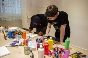 A photo of 2 Stella's Place Peer Support Workers painting, with a big spread of colourful art supplies spread out in front of them.