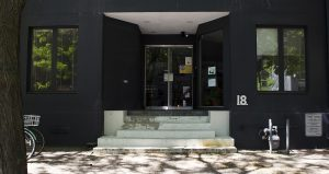 A photo taken on a sunny summer day in front of the Camden Street location of Stella's Place. The image features the front of the black building, in front of the stairs leading to the front door. There are shadows from the tree above on the foreground.