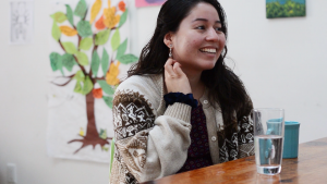 A photo of Victoria sitting down, laughing and looking to the right. Victoria has their hand up tucking hair behind their ear and is sitting in front of a wood table. In the background is a white wall with a drawing of a tree hung up on the wall.