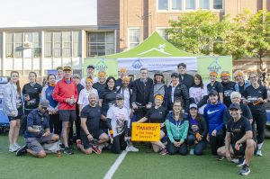 A group photo of a few dozen people smiling into the camera. The photo was taken outside on a sports field outside of a red brick school before a 5K run. John Tory is in the middle of the photo and behind them all is the Stella's Place tent with the logo and two banners on either side.