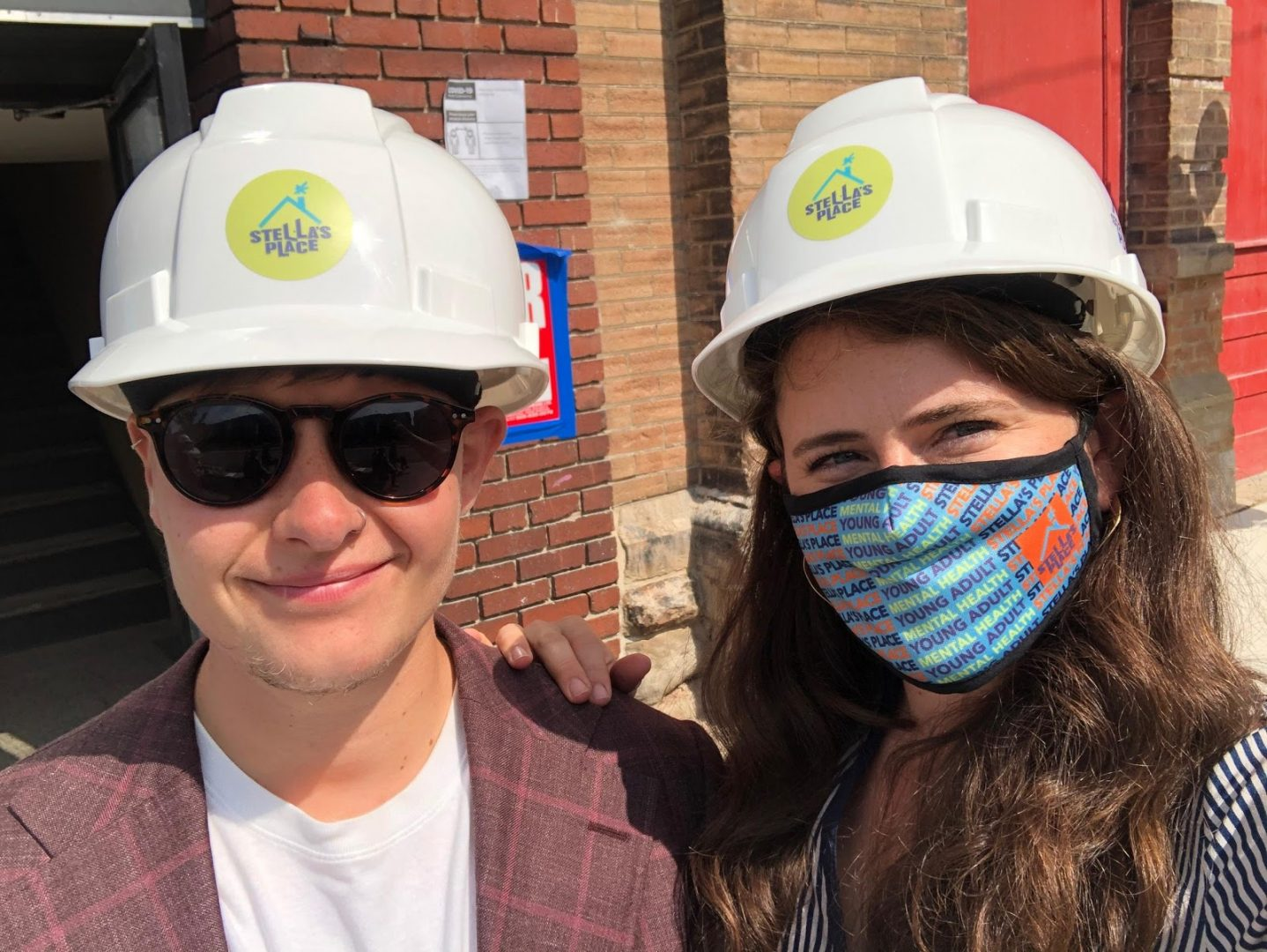 Elisa and Stella posing together in hard hats that have a Stella's Place sticker on the front. Stella is wearing a brightly coloured Stella's Place face mask and Stella is wearing black sunglasses.