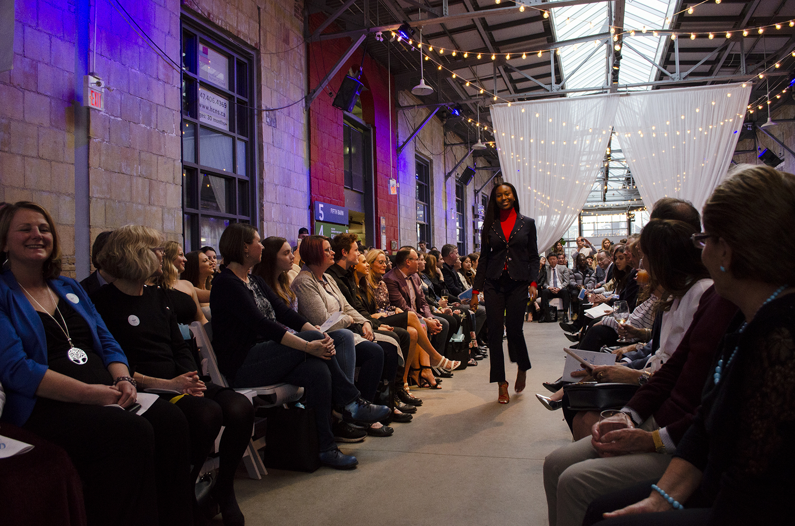 A photo of a fashion show with a model walking down a runway lined with people in the audience sitting down. The image is mostly dark with light coming in from windows in the ceiling above and a bright purple neon light in the left corner. There are small yellow string lights hung up in the background.
