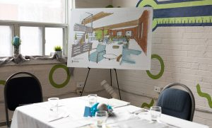 An image from an event at Stella's Place showing an empty prepared table with a tablecloth and table set. Behind the table and beside a window is a big canvas of a sketch of the new Stella's Place building, sitting on an easel.