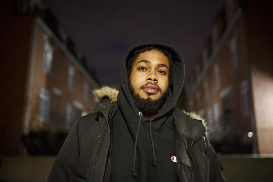 A portrait of Jah-Reign Taylor looking into the camera with a serious expression, wearing a black hoodie pulled over their head and overtop wearing a dark green winter coat. The picture was taken at night with a flash and the background is dark behind.