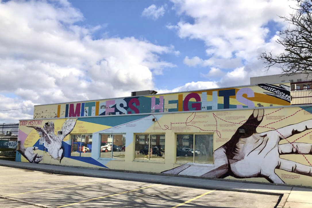 """A photo of a colourful building, taken outside on a bright cloudy day. The building has large multi-coloured hand drawn letters at the top that reads """"Limitless Heights"""". Underneath on the yellow brick of the building are illustrations of hands stretched out."""