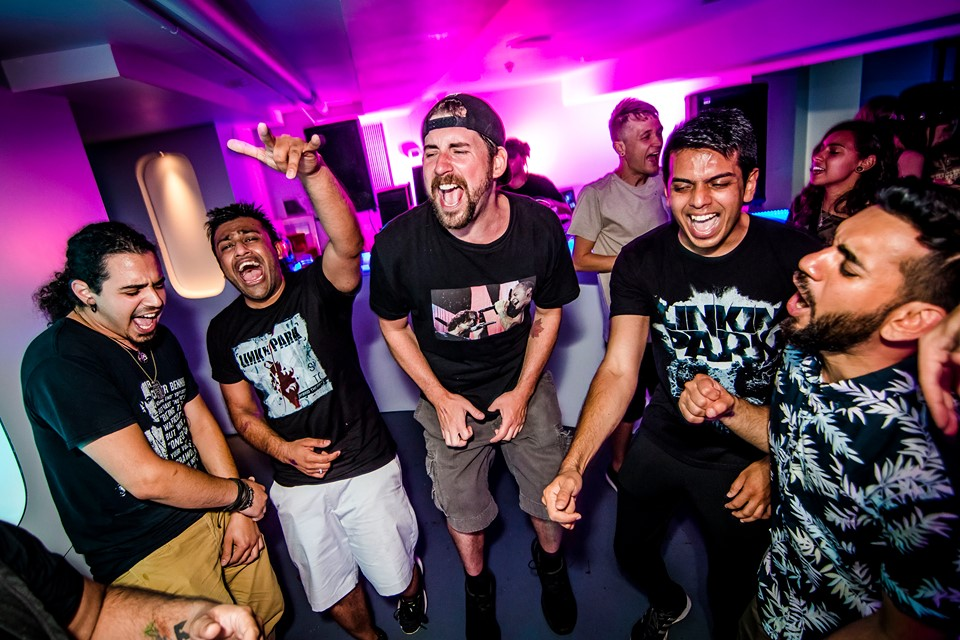 A group of people singing passionately to Linkin Park, wearing merch at the Chester Bennington Tribute Party