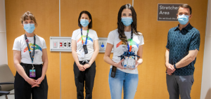 4 people standing side by side but spaced apart, posing for the camera. Each person is wearing a blue face mask. They are standing in front of a wooden wall.