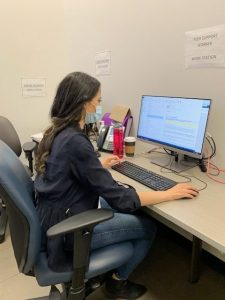 """Yolanda sitting at a computer. There's a sign above the monitor that reads """"Peer Worker Work Station"""""""