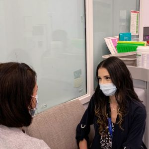 Yolanda, a Peer Support Worker speaks to a patient in an office room