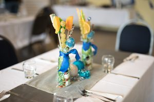 A closeup photo of a table centerpiece. The focus is on the decoration which is a clear vase filled with colourful objects and slices of orange and grapes on sticks standing in it, and tied in a dark blue bow. The table around it is blurred out.