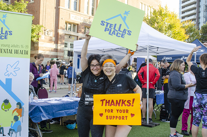 """A photo of 2 people at the Yorkville Run holding signs up in the air and smiling for the camera. The person on the left is holding a green canvas with the Stella's Place logo and the person on the right is holding an orange sign with letters """"THANKS! For your support"""". In the background behind them is a crowd of people."""