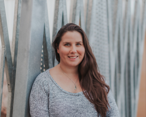 A portrait of Allison, sitting against a large metal structure. Allison has long brown hair, is wearing a small necklace and a grey longsleeve shirt. She is smiling into the camera.