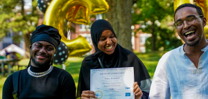 A portrait of 3 people laughing. The person in the middle is wearing a black headscarf and is holding a white paper certificate up. The person on the left is also wearing a head covering and a black shirt with a silver necklace. The person on the right is wearing glasses and a white button up shirt. They are standing in an outside space in summer, the background is filled with green grass and trees.