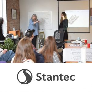 A photo of a bunch of people in a room looking towards the front at someone speaking with the Stantec logo at the bottom in black