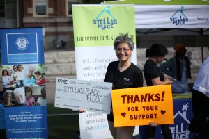 """A photo of Stella's Place supporter Nancy Seto holding two signs. The sign on the left is a large cheque poster made out to Stella's Place for $1,000. The poster on the right is an orange sign that says """"Thanks for your support"""" in black."""