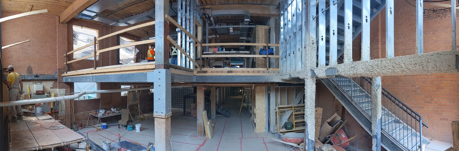 A panorama photo of the construction site at 54 Wosleley showing 2 floors with exposed beams and construction tools.