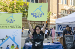 A supporter holding up a green Stella's Place banner straight above their head at the Yorkville Run. Behind them are crowds of people around booths.