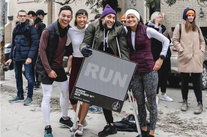 """A group of people outside posing a picture and holding a banner that says """"RUN"""""""