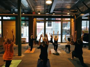 A photo taken of a group of people stretching, it's taken behind the people with their backs facing the camera and looking out through a window. Everyone in the room is on a yoga mat and has their arms stretched out tall above their heads in unison.