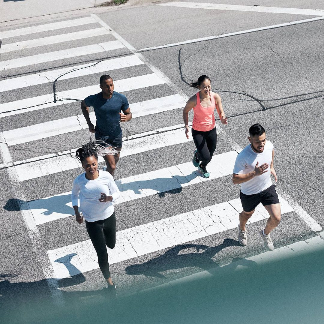 A top down photo of 4 people running on a street crosswalk with white stripes on the pavement.