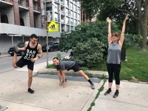 A photo of 3 Stella's Place staff stretching before a run on the sidewalk in a park.