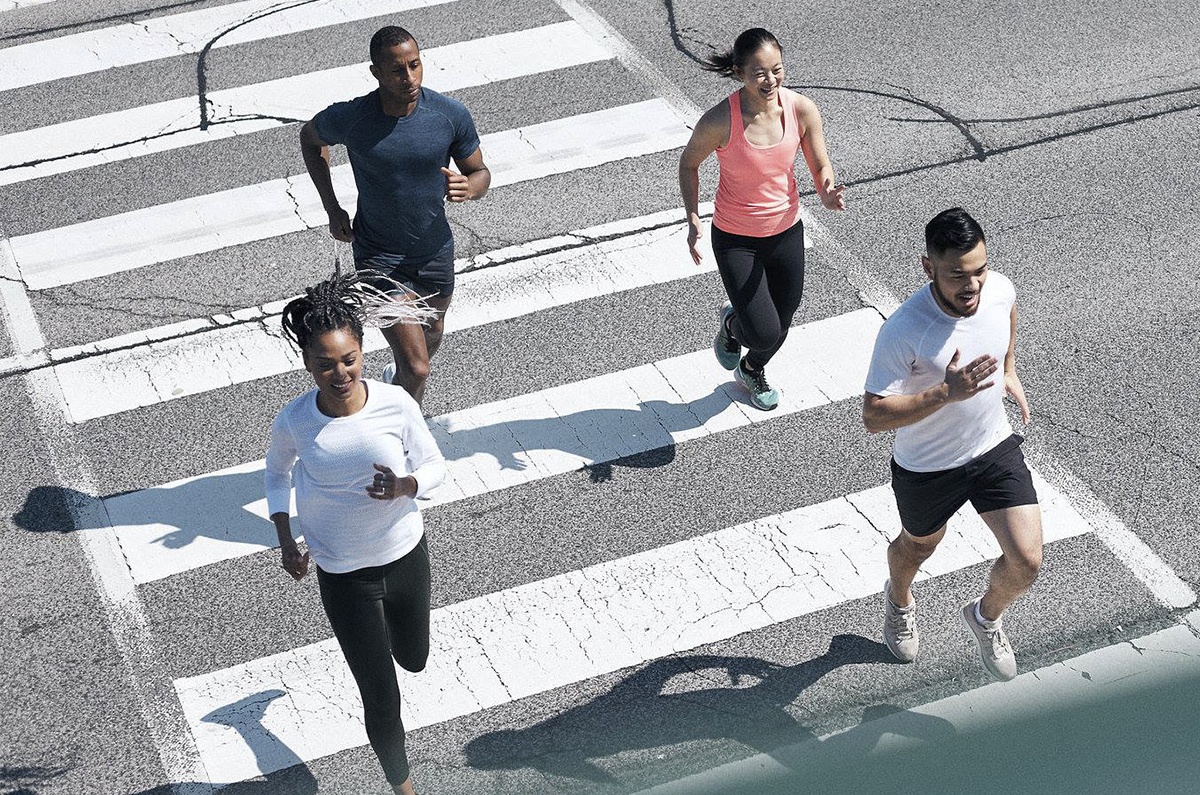 A top down photo of 4 people running across a road crosswalk